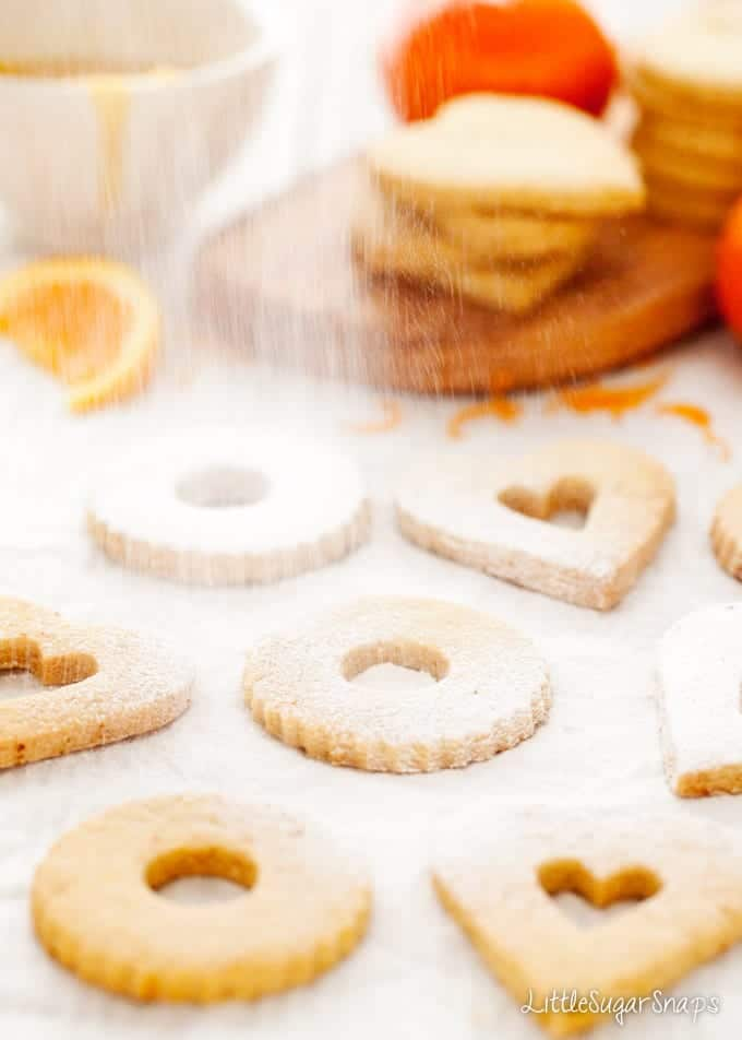 Heart and circle cut out cookies being dredged with icing sugar