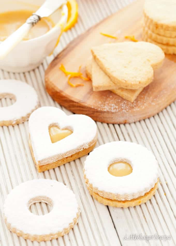 Linzer Cookies being sandwiched together with orange caramel spread