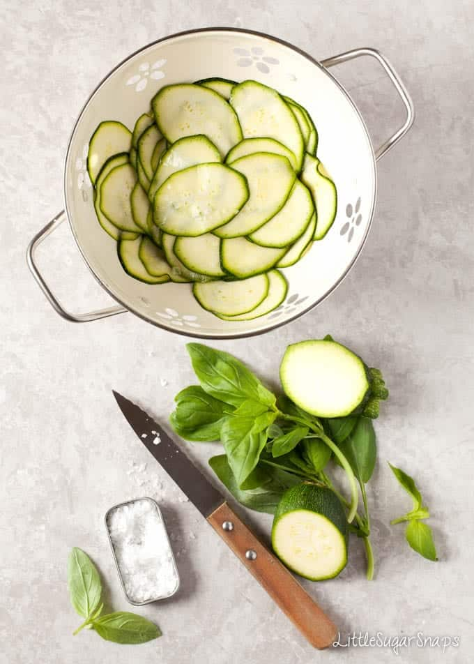 Sliced courgette in a colander being salted