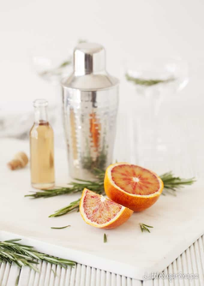 Cut up blood orange, rosemary and syrup next to a cocktail shaker