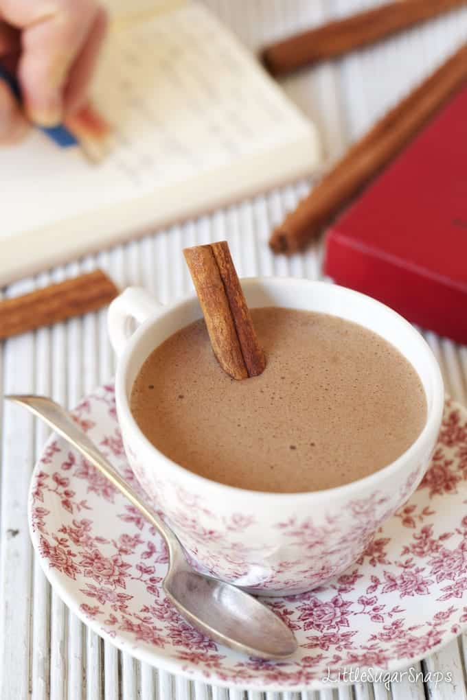 A cup of frothy hot Chocolate with a cinnamon stick