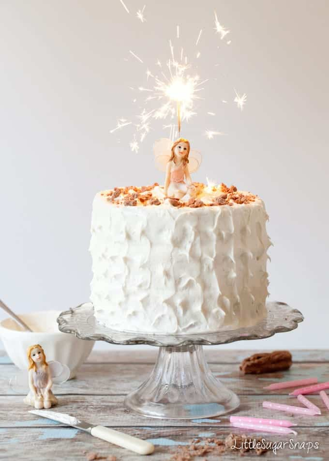 Birthday cake with marshmallow frosting, a lit sparkler and a fairy ornament on top. Ingredients, such as frosting and chocolate flakes are nearby along with pink candles.