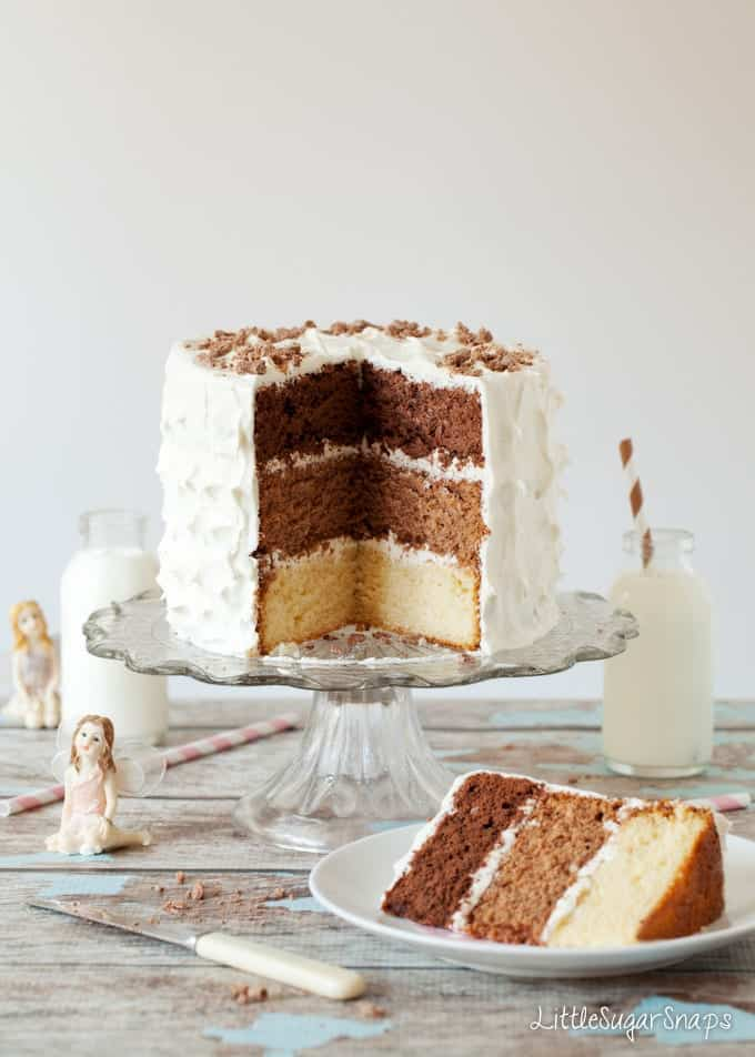 A triple chocolate layer cake with 3 layers of chocolate sponge (white chocolate, malted milk chocolate and dark chocolate). They are all stacked up and covered in white marshmallow fluff buttercream. The cake is cut open and a slice in a a plate in front. There are decorative fairies and bottles of milk in view