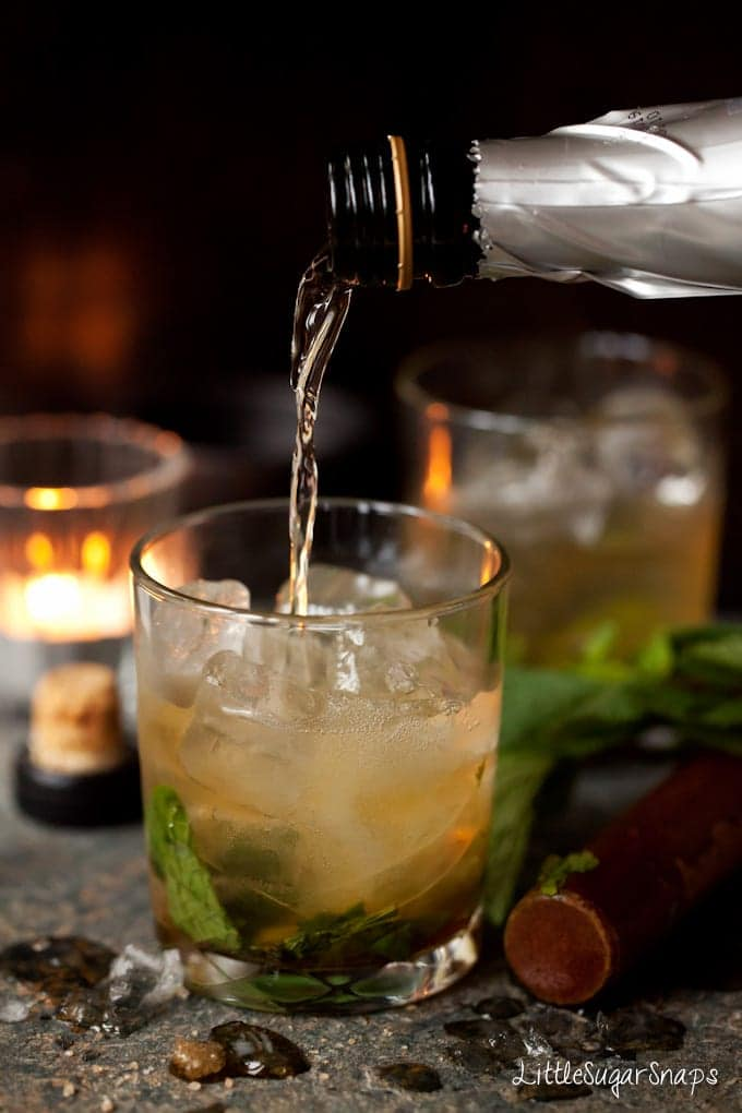 Prosseco being poured into a glass with whiskey and fresh mint