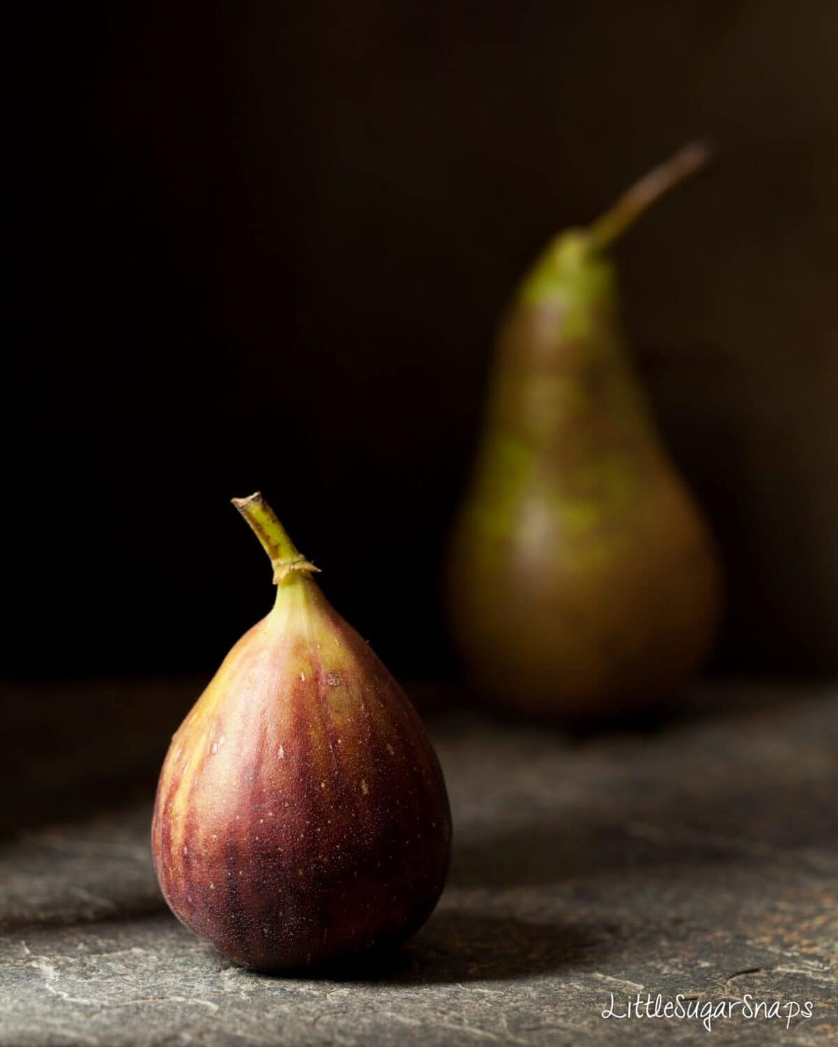 A fresh fig with a pear in the background