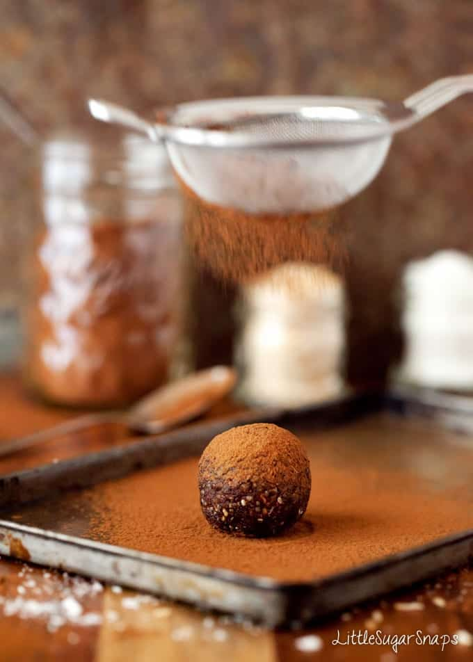 Chocolate Energy Ball being dusted with cocoa powder