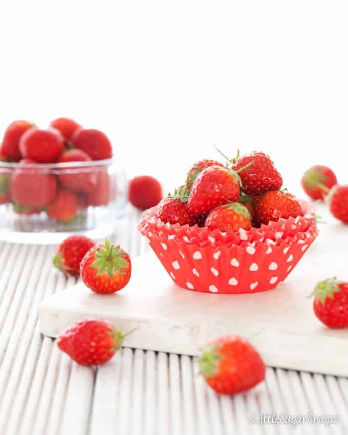 Strawberries in red cupcake cases with white polka dots