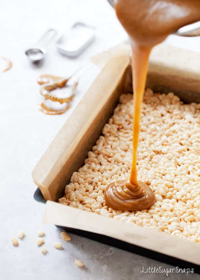Pouring caramel over a rice krispie treats layer in a baking tin