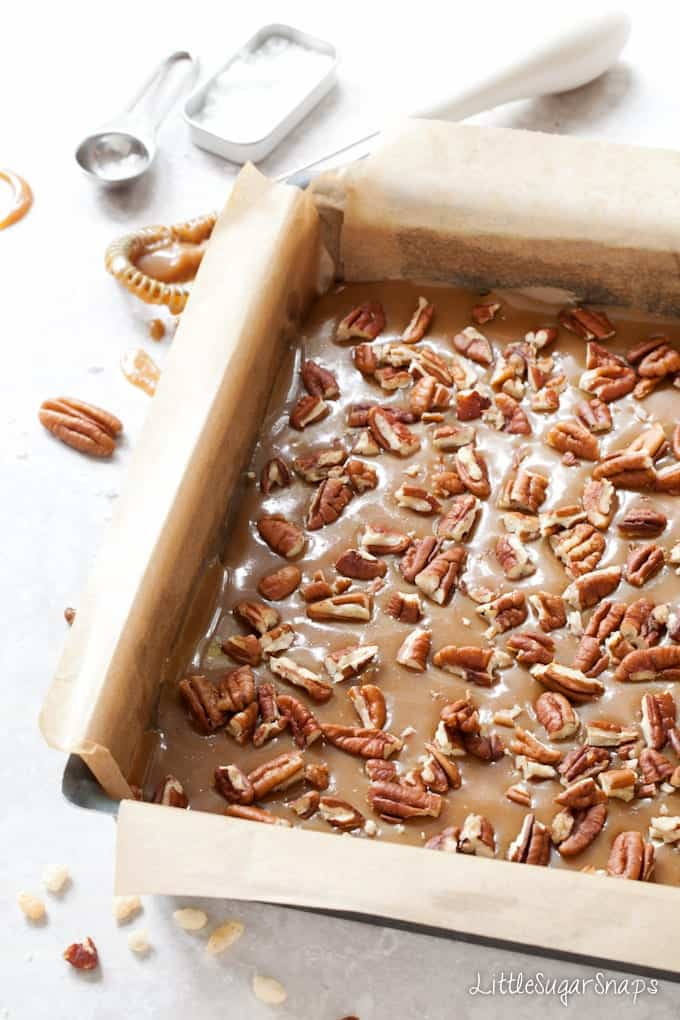 Pecan nuts sprinkled over caramel in a baking tin