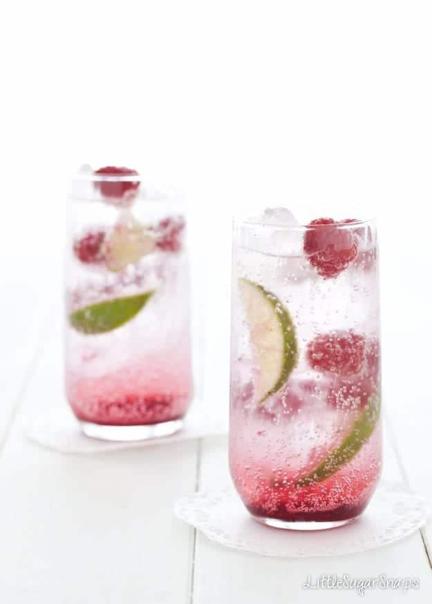 Hibiscus Raspberry Soda drinks with lime and raspberry garnish
