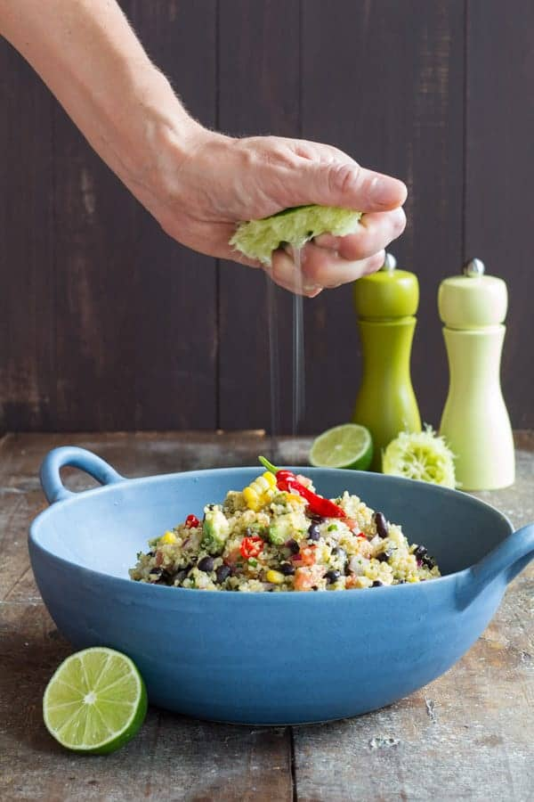 person squeezing lime juice over Mexican Quinoa Salad