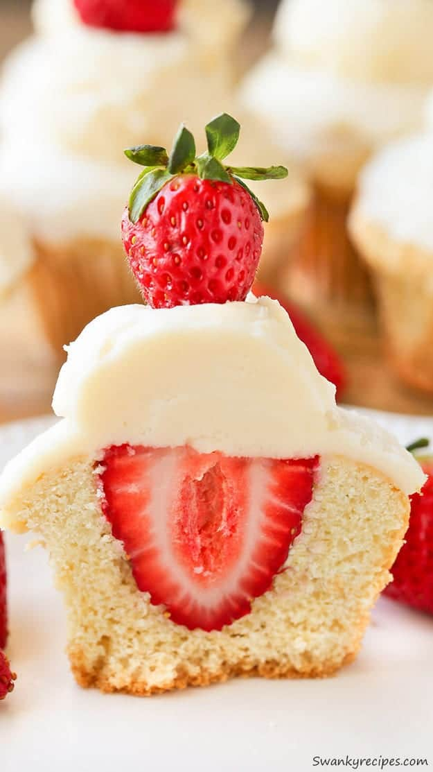 A Strawberry Shortcake Cupcake cut in half to reveal a strawberry in the centre