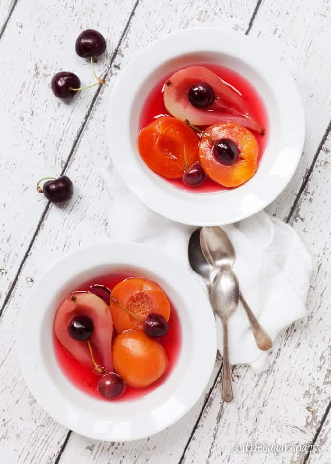 Bowls of Poached Fruit in cooking syrup including pears, cherries and apricots