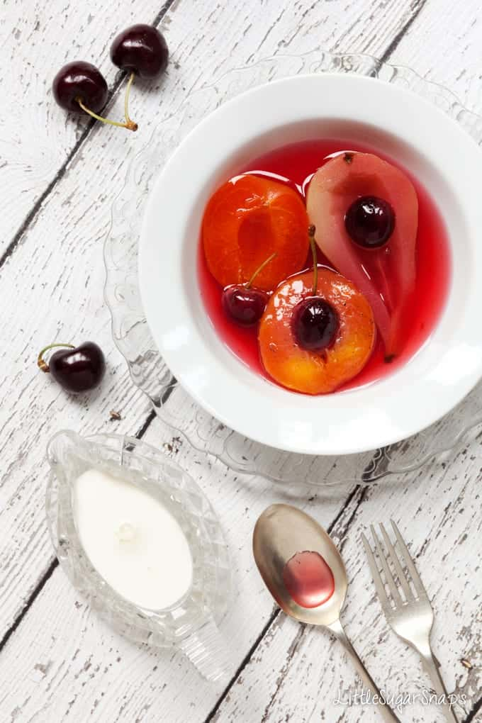 A bowl of Poached Fruit including pear, peach and cherries
