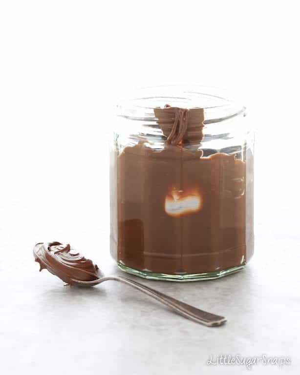 A jar of chocolate spread with a teaspoon at the side
