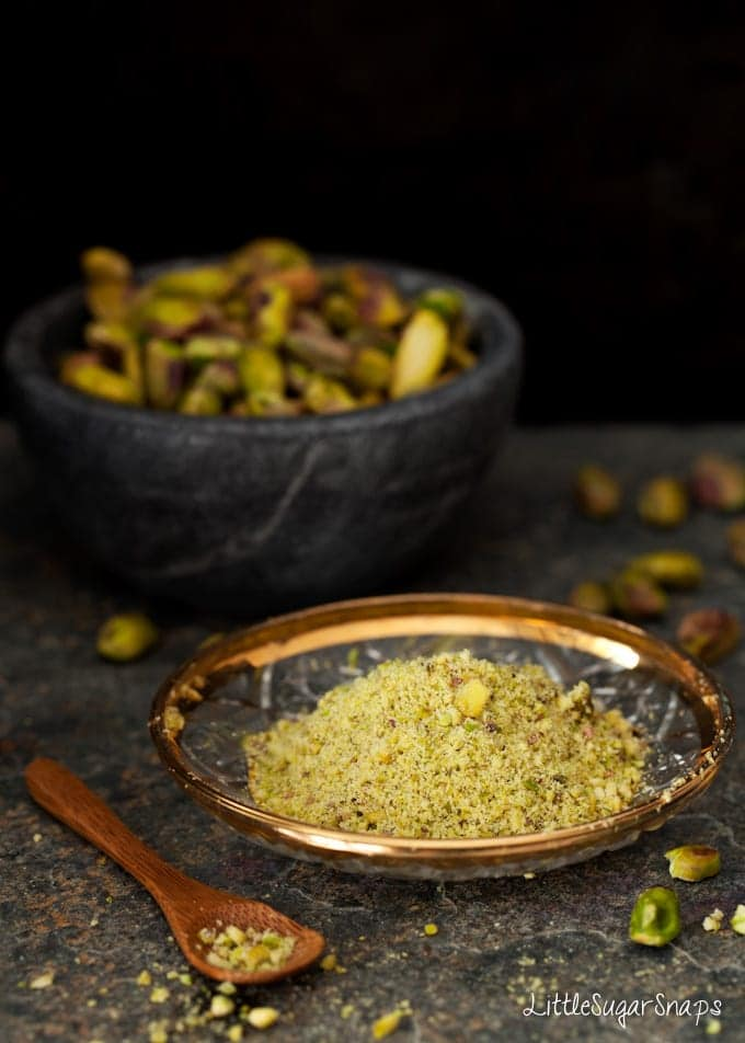 ground pistachio nits on a small plate with a bowl of whole nuts in the background