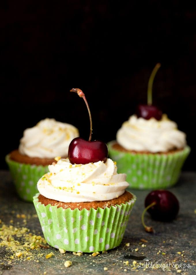Three pistachio cupcakes decorated with mascarpone frosting and a fresh cherry