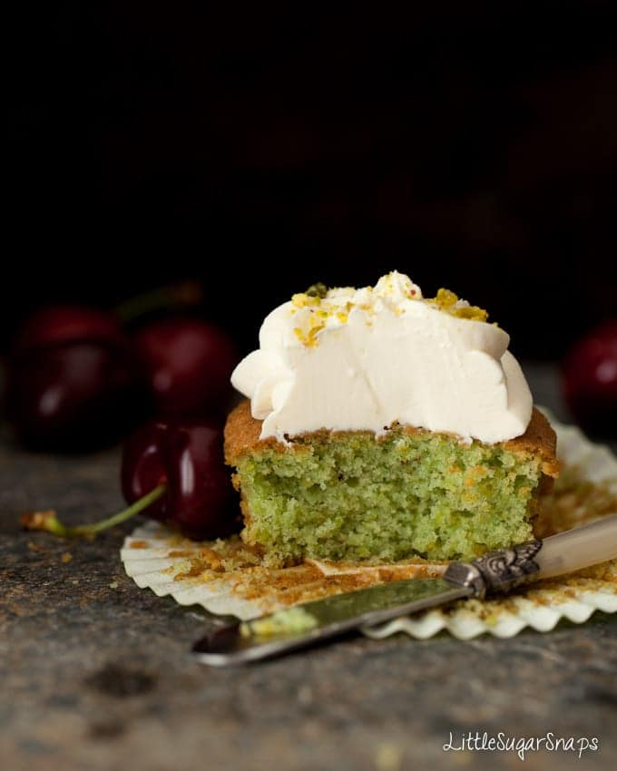 Cut open pistachio cupcake revealing a green sponge. Topped with mascarpone frosting