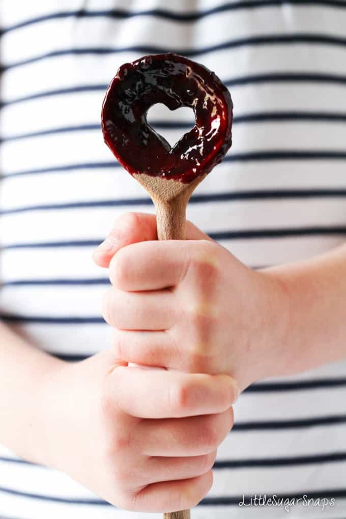 Fruit sauce on a spoon being held by a child.