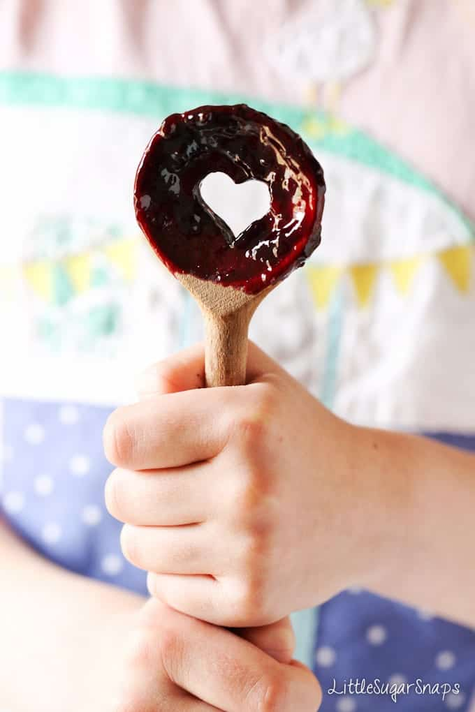 Child holding a wooden spoon with fruit sauce on it.