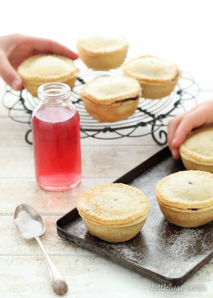 Children picking up small Blackcurrant Pies from baking sheets