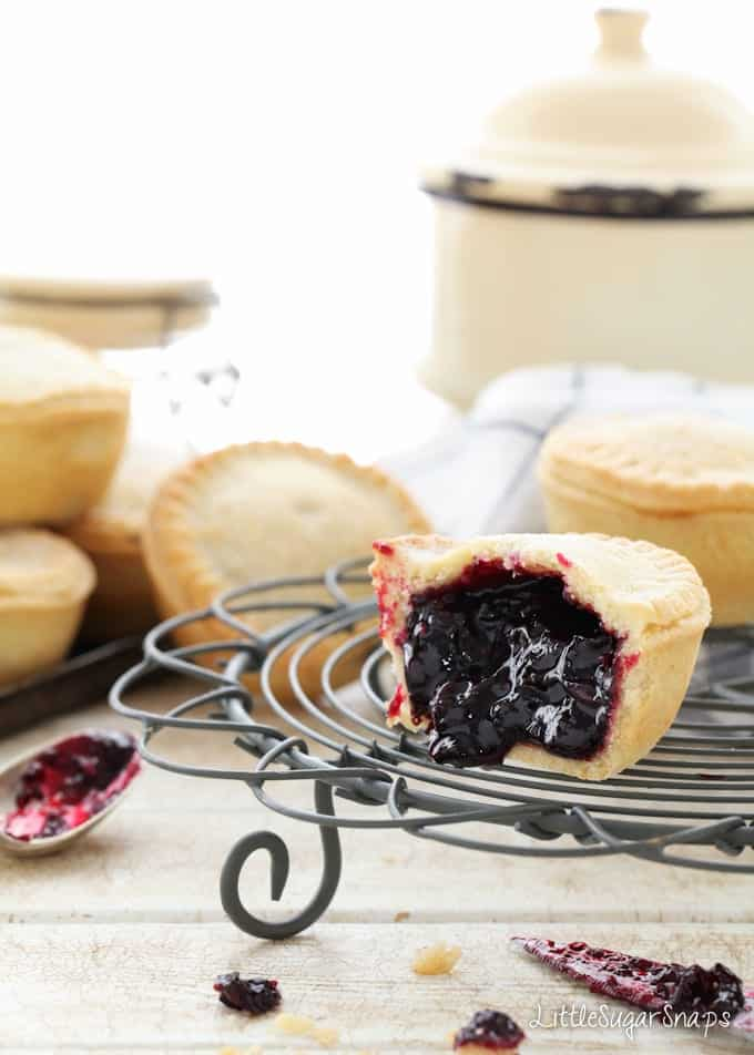 Blackcurrant pies on a wire rack - one is cut open.