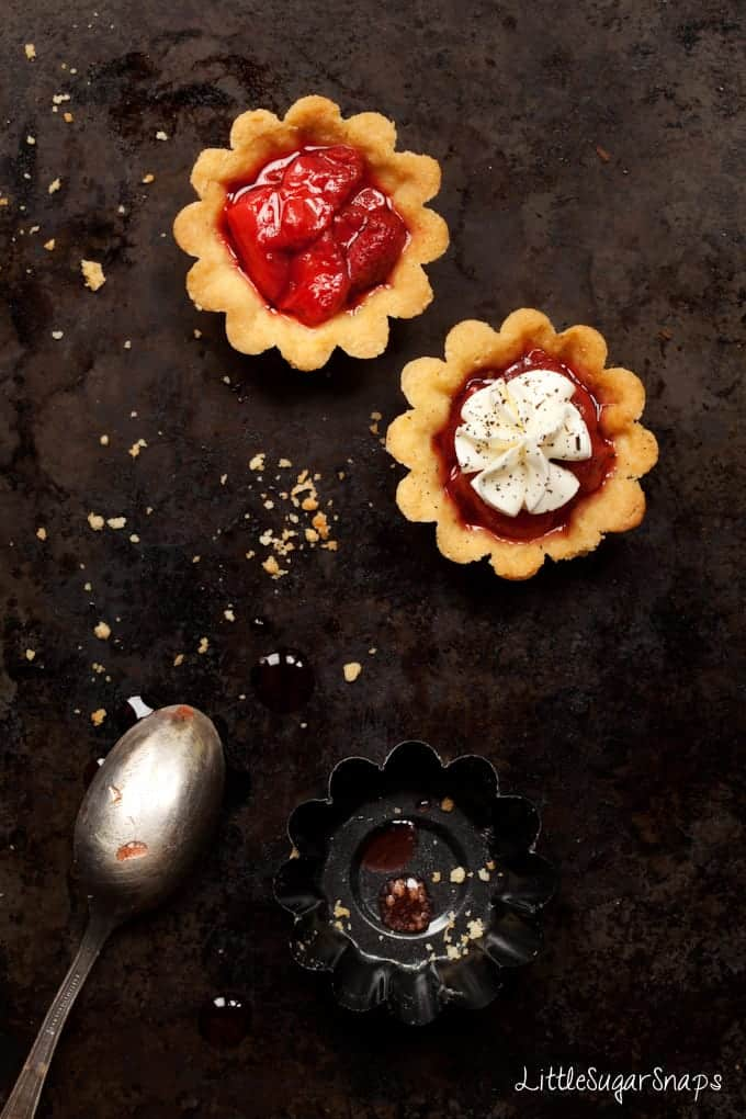 Two small Strawberry tarts - one is topped with piped cream.
