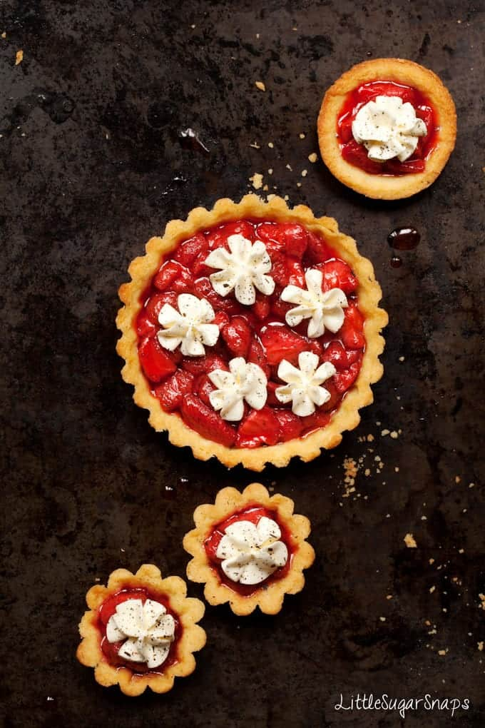 Strawberry Tarts topped with whipped cream and ground vanilla