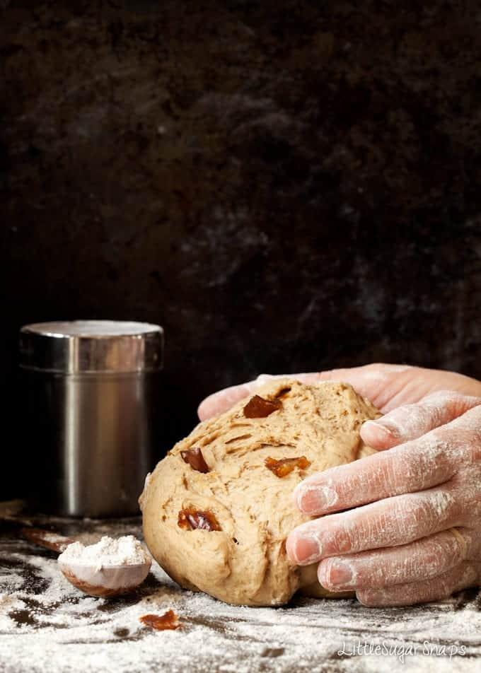 Person kneading dates into bread dough.