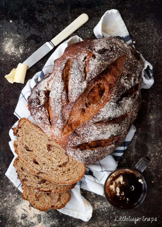 A loaf of Coffee Date Rye Bread with slices cut from it.