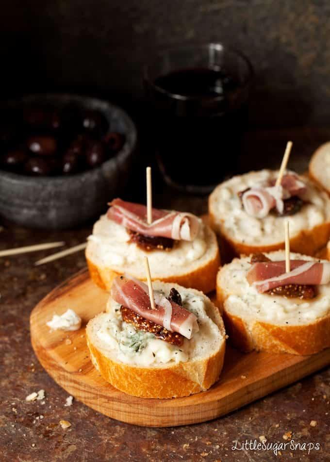 Fig, prosciutto and gorgonzola crostini on a wooden board.