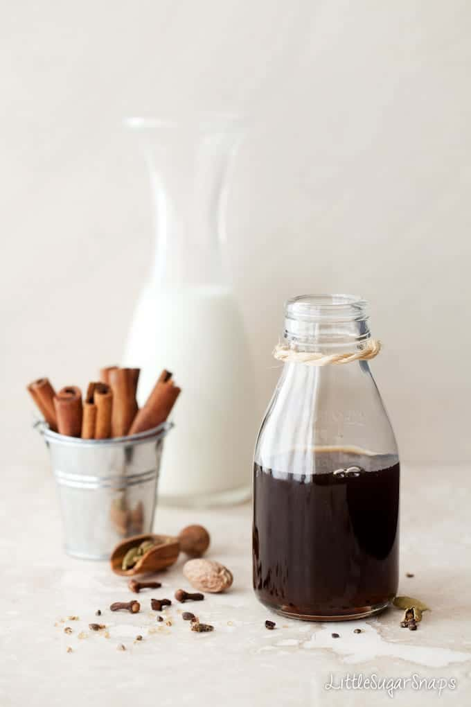 A bottle of Masala Chai Syrup next to spices.