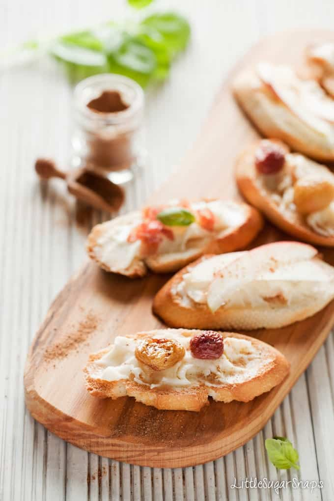 Taleggio Crostini on a wooden board with mixed toppings
