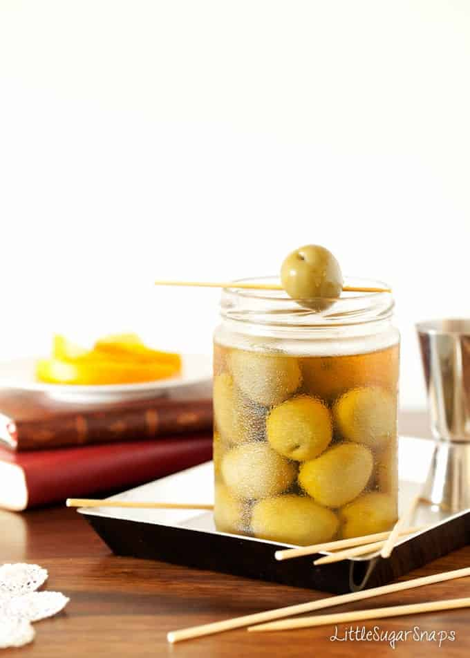 A jar of green olives with one resting on top.