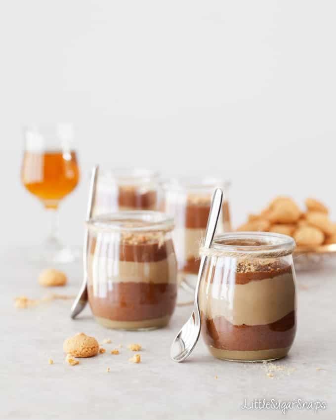 Layered chocolate, coffee and caramel desserts in glass jars