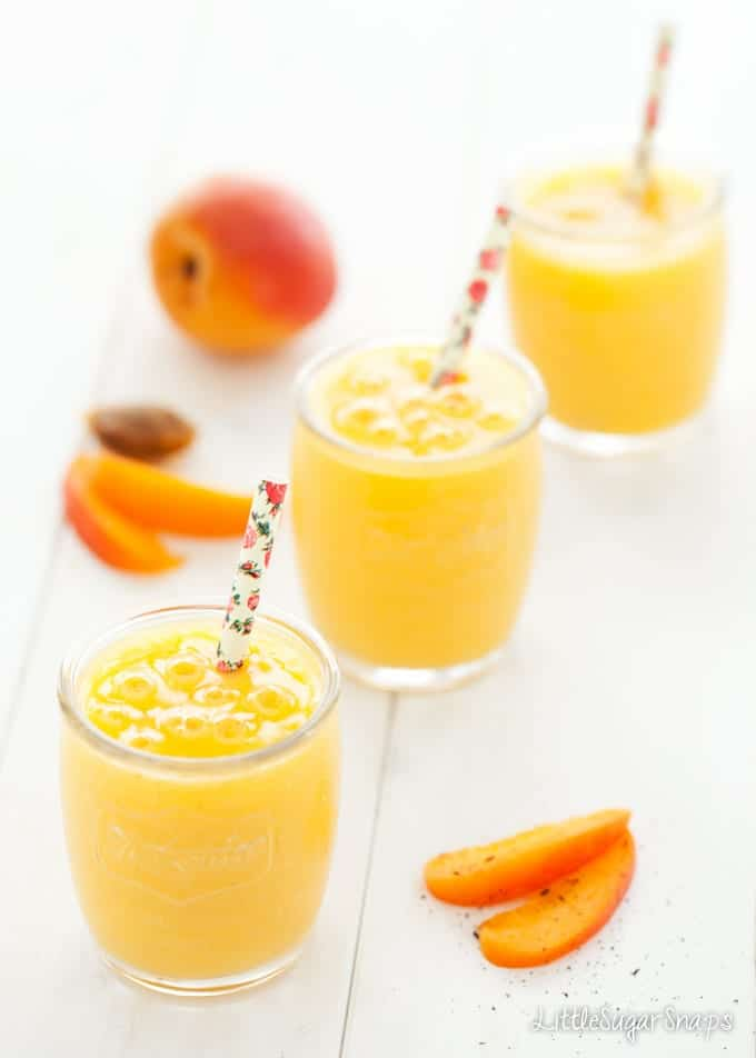 Three glasses of apricot smoothie in a diagonal row