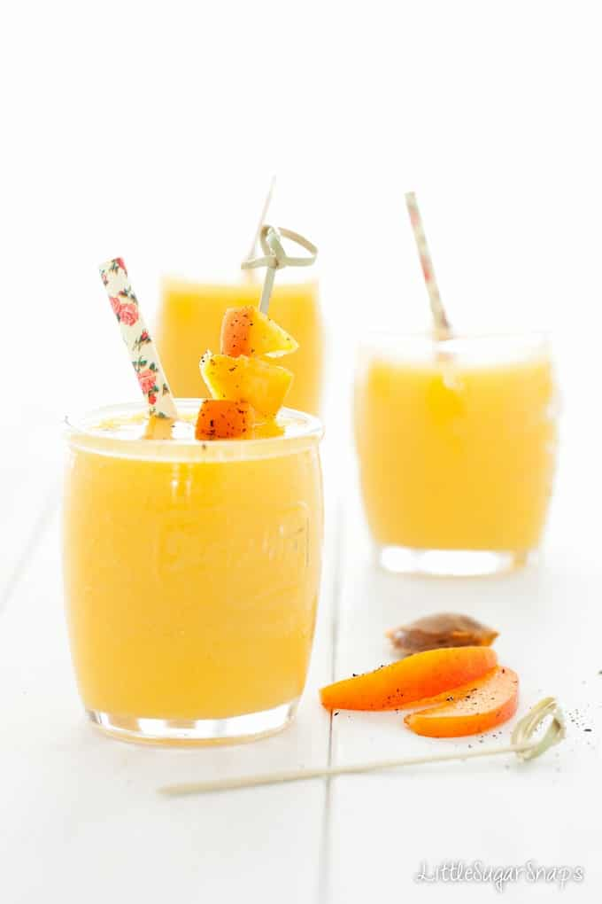 Yellow mango smoothie with apricot garnish and a paper straw