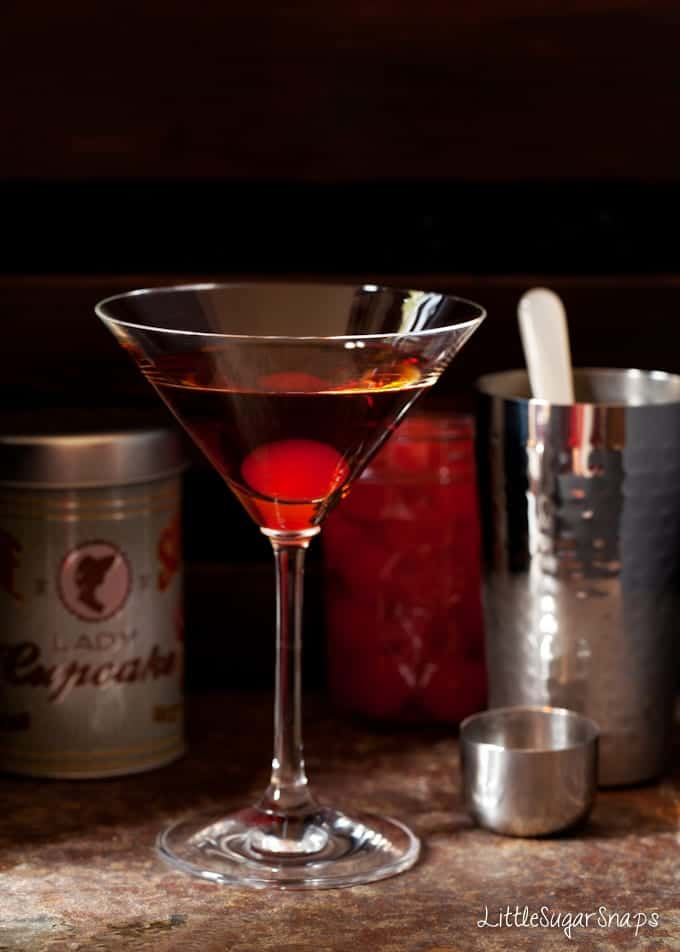 bourbon cocktail with a maraschino cherry in the glass