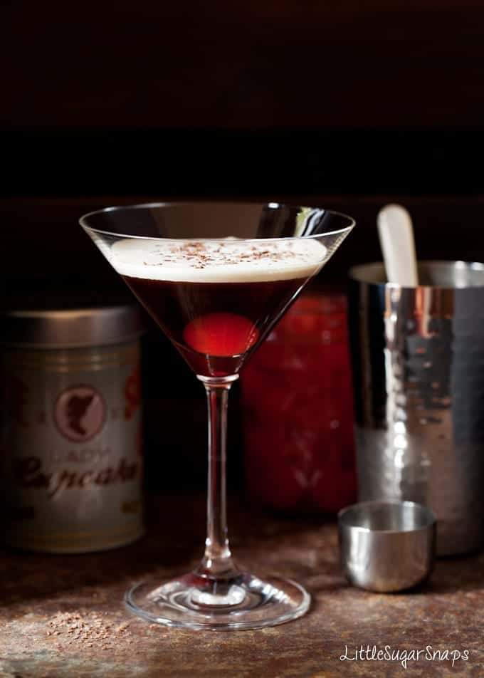Bourbon Black Forest Cocktail with a float of cream and grated chocolate and a maraschino cherry in the glass