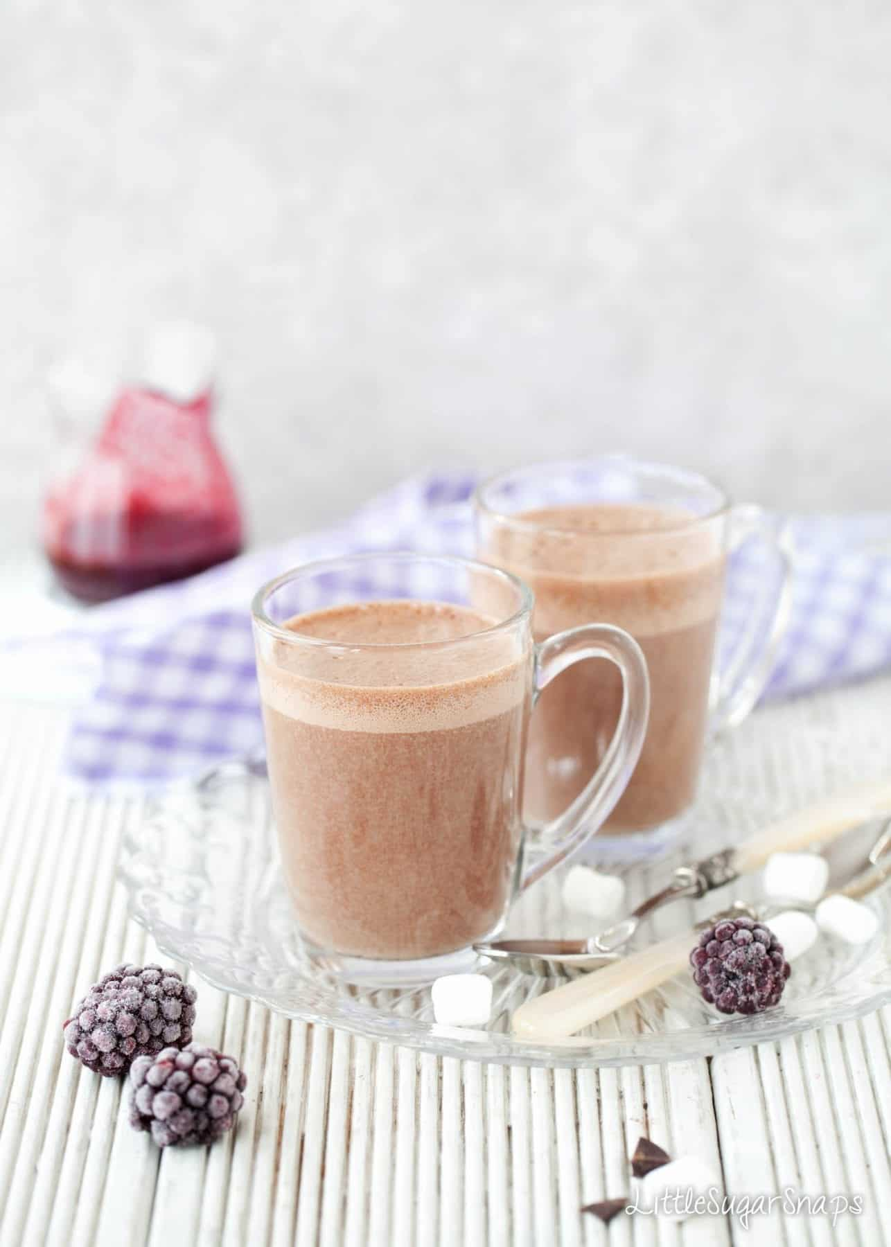 Glass mugs of Hot chocolate drink with a frothy top.