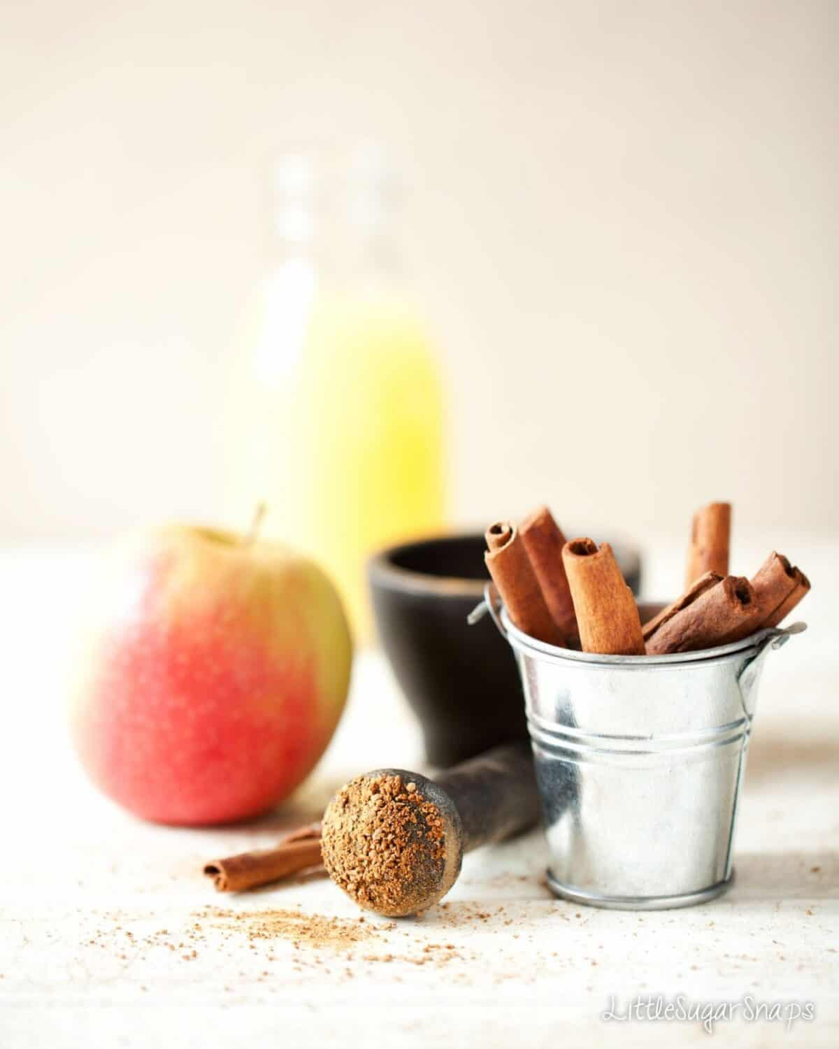 A small bucket of cinnamon sticks with ground cinnamon, apple and fruit juice