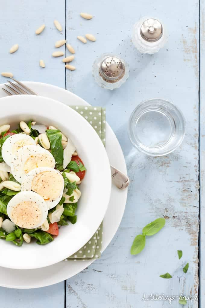 Bowl of pasta, spinach & tomato salad with sliced egg