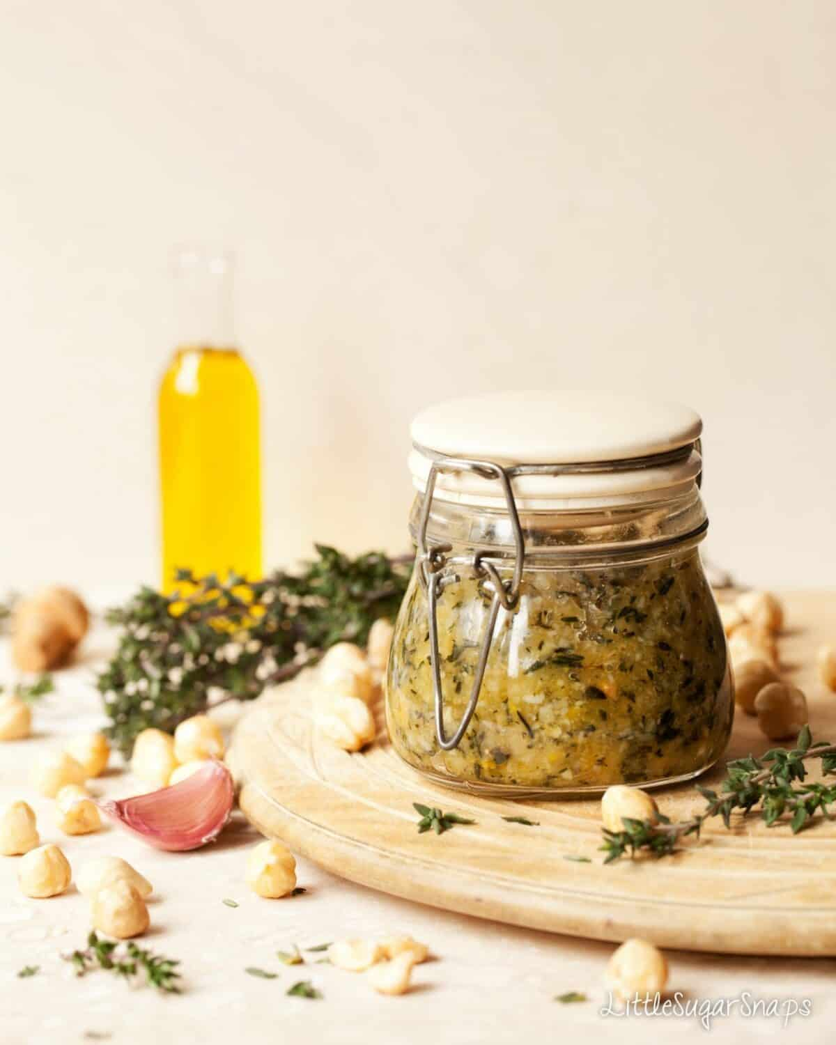 A jar of homemade hazelnut and thyme pesto on a wooden board with ingredients in shot, including garlic, olive oil, hazelnuts and fresh thyme