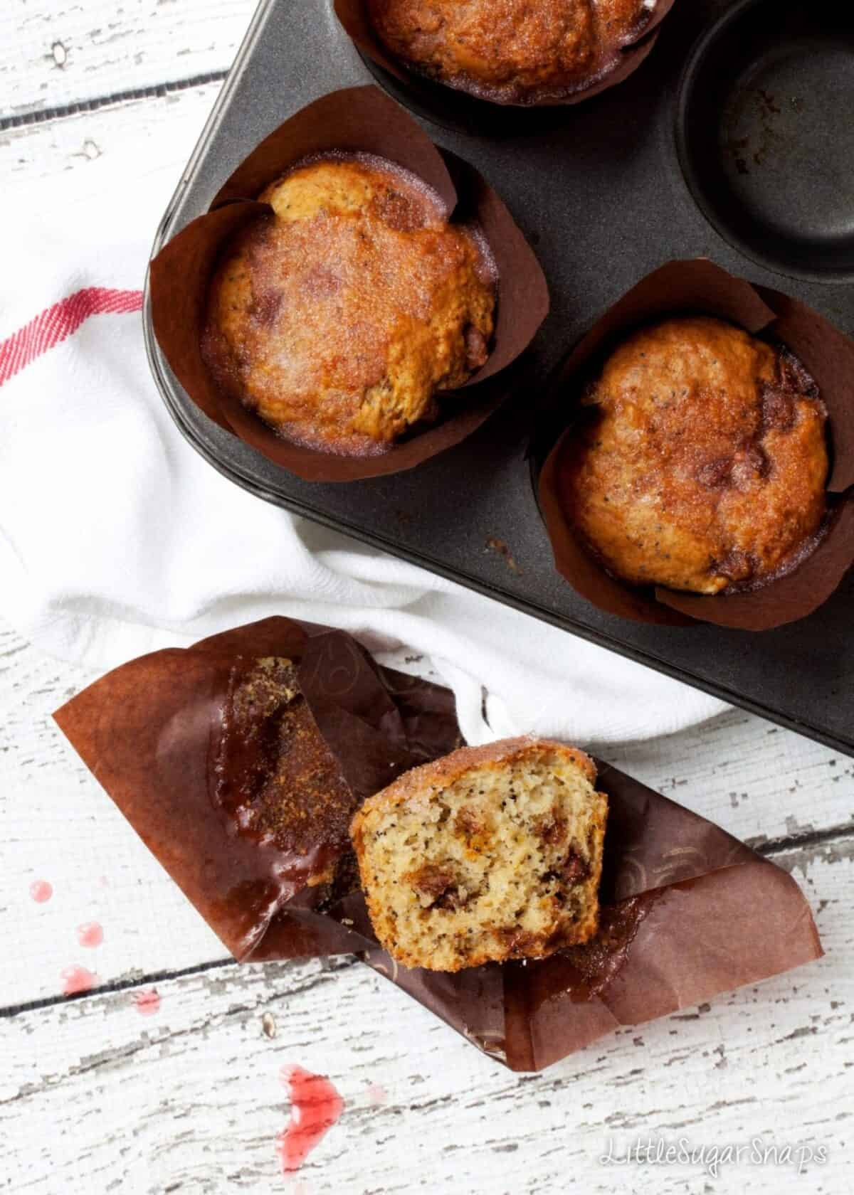 A tin of Orange Drizzle Muffins with one part eaten on the table.