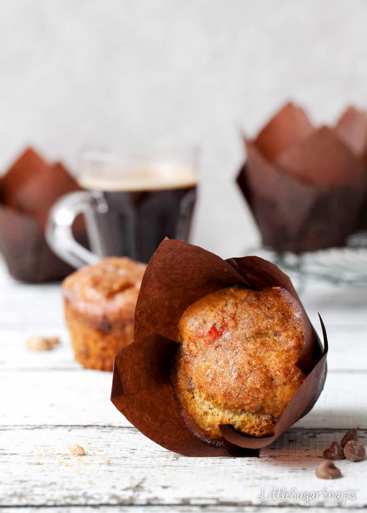 An Orange Drizzle Muffin on its side - still in a brown wrapper