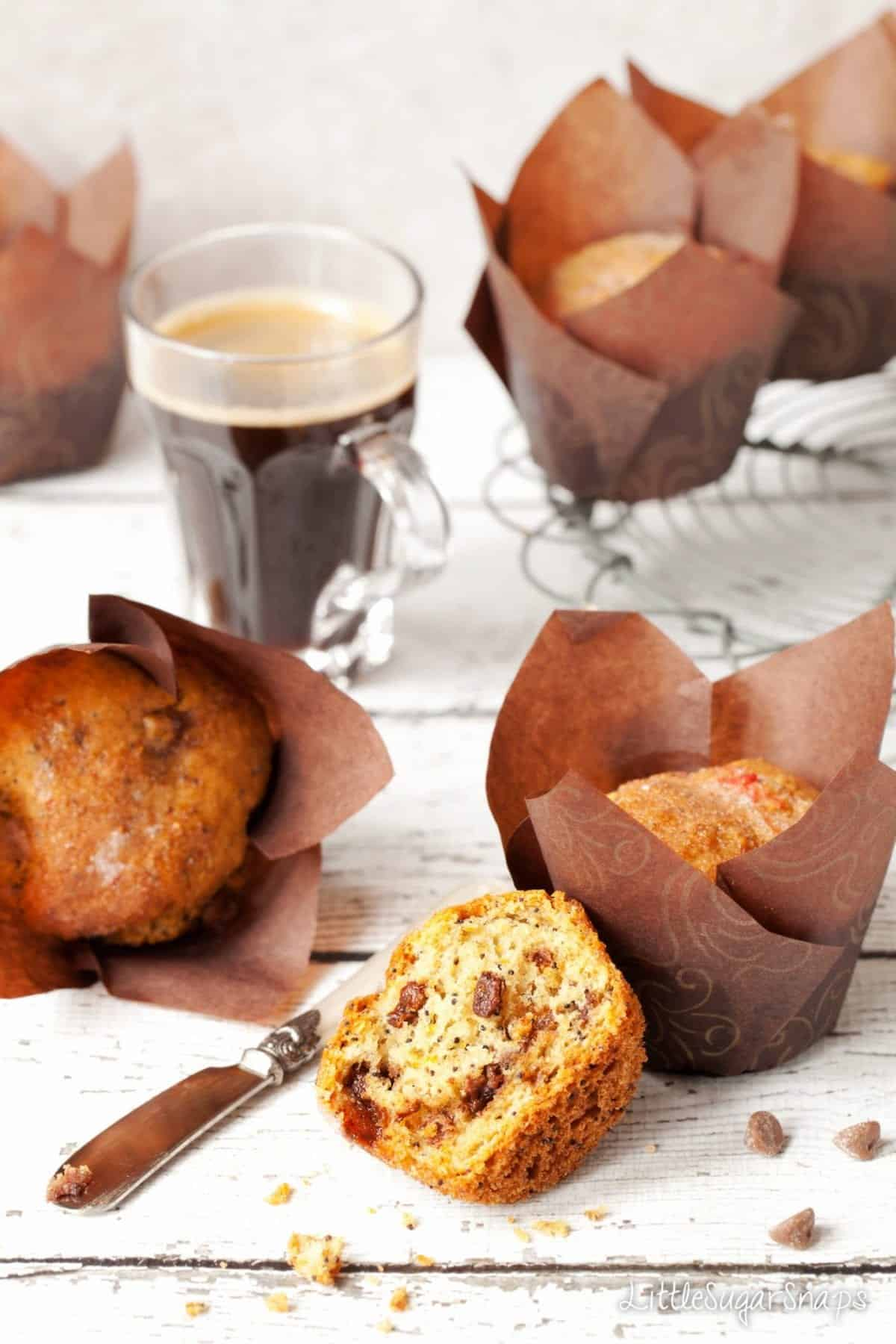 Chocolate orange muffins on a table with a cup of coffee.