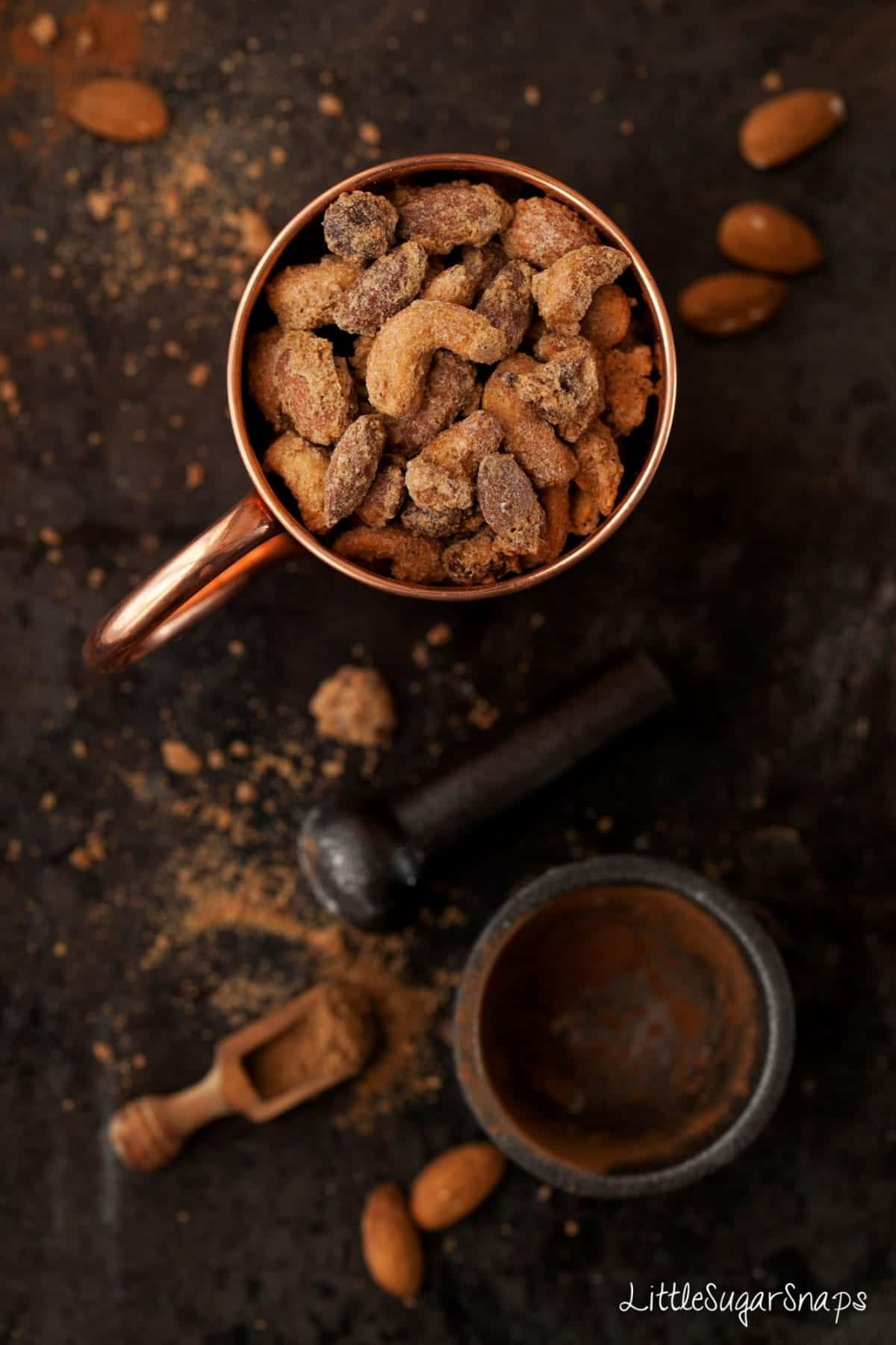 Chai spiced candied nuts in a copper mug.