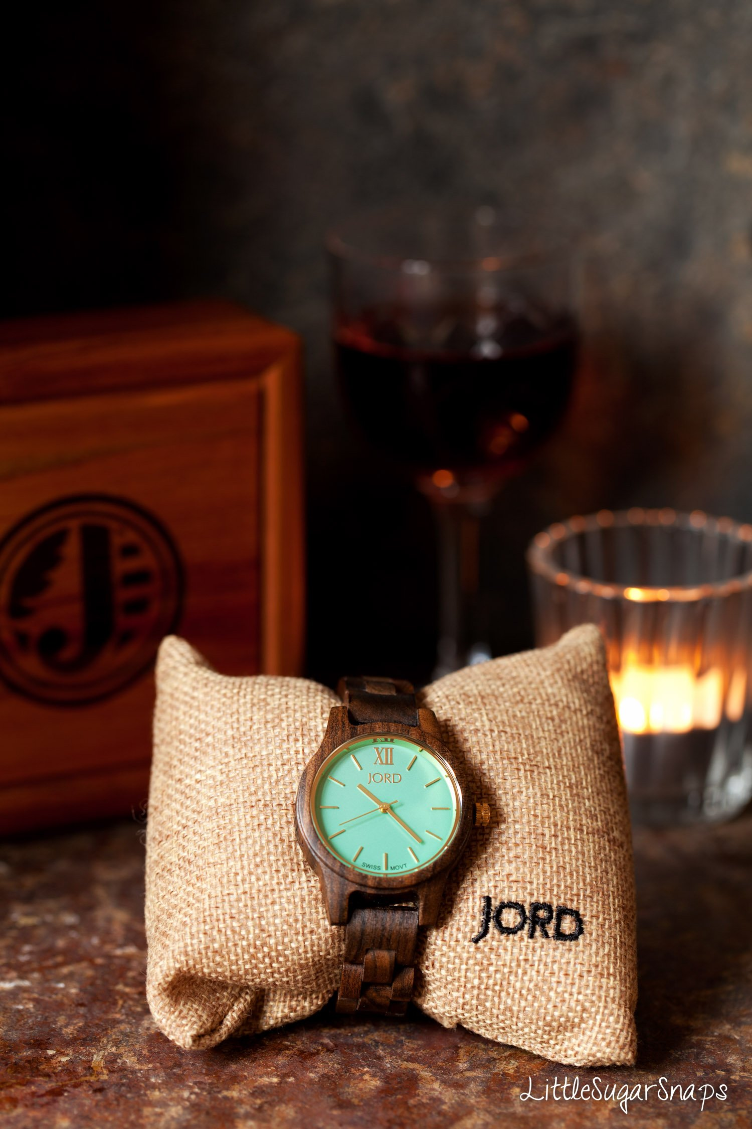 A wooden watch wrapped around a hessian pillow