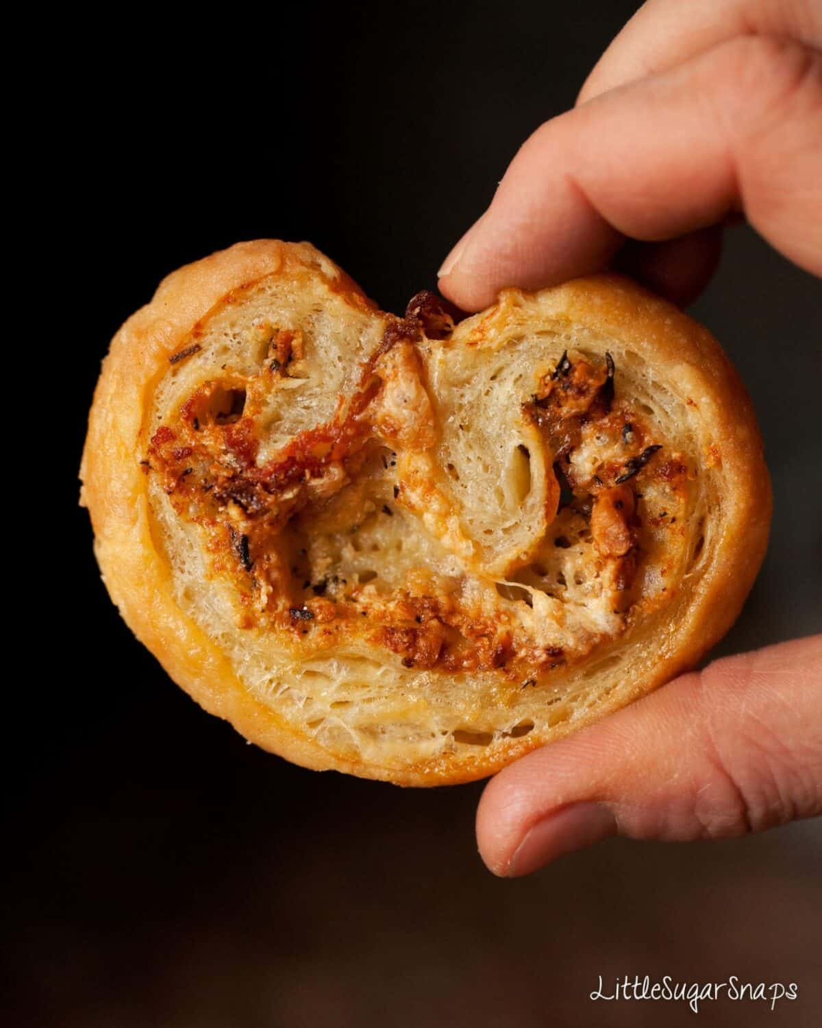 Person holding a Cheese Palmier against a black background