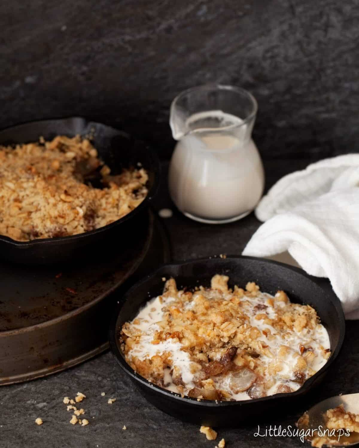 Chocolate Pear Crumble in a small skillet with cream poured on.
